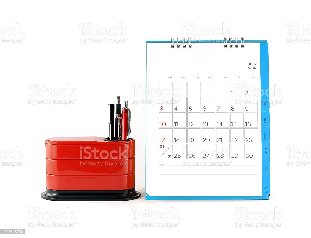 blue desk calendar in july 2016 and red desk organizer stock photo