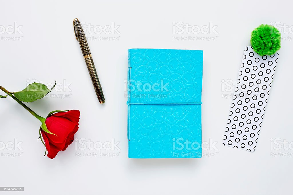 Blue diary with bookmark pen and rose on white background stock photo