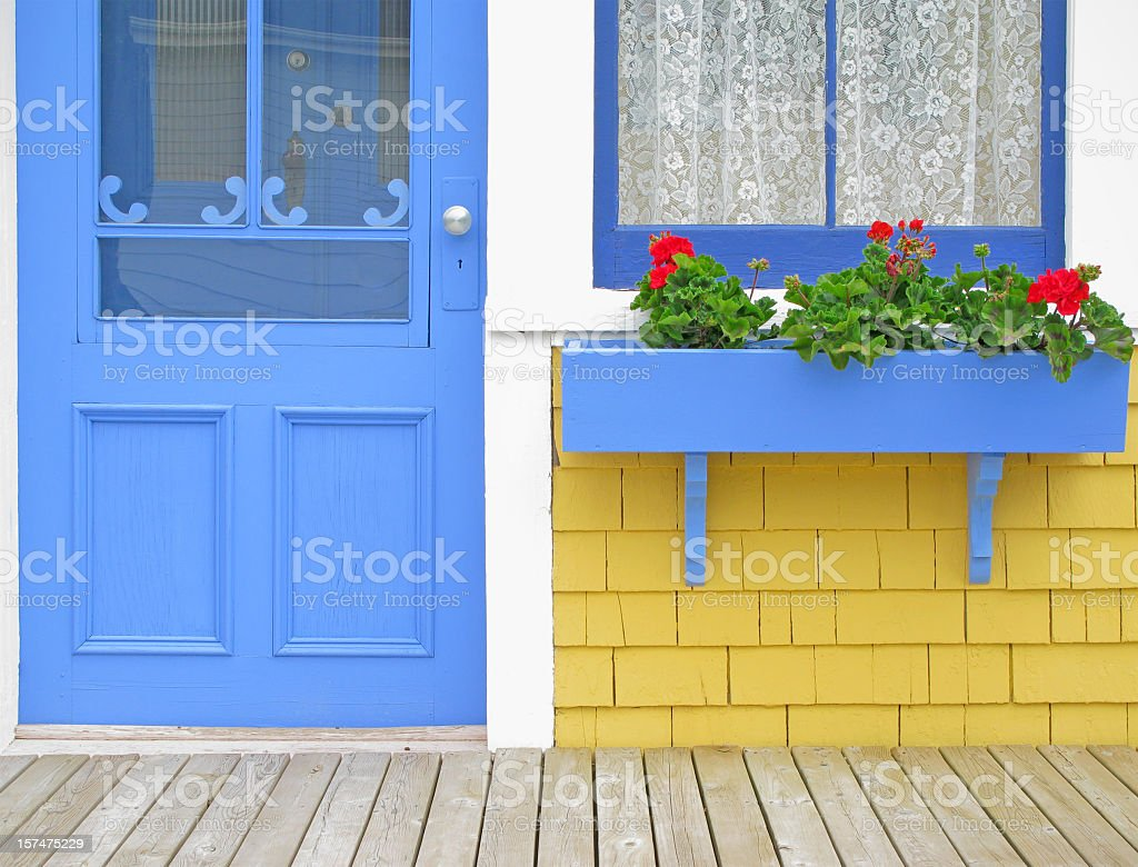 Blue door and window box with Geraniums. stock photo