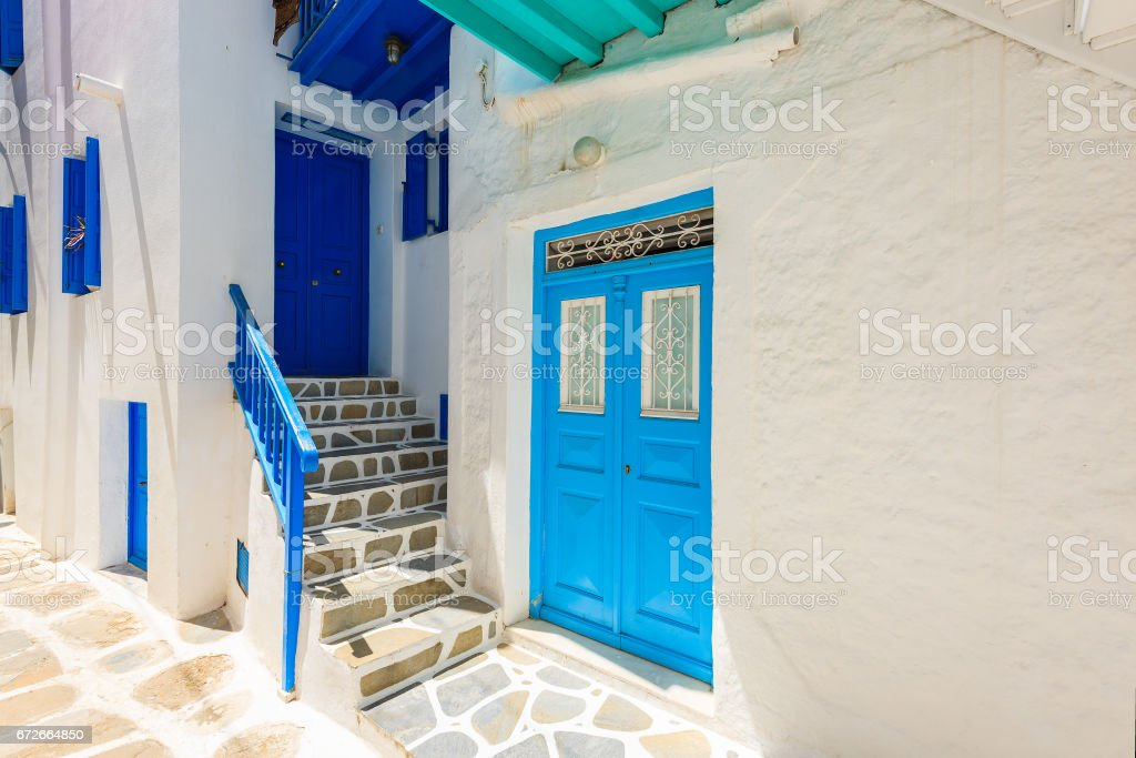 Blue door and windows of typical house on street of beautiful Mykonos town, Cyclades islands, Greece stock photo