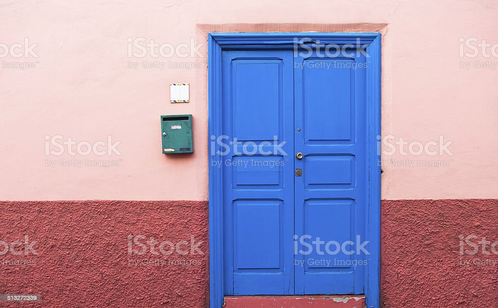 blue door in pink wall stock photo