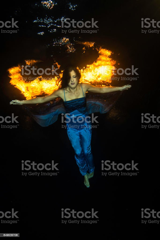 Blue dressed girl with firewings underwater stock photo