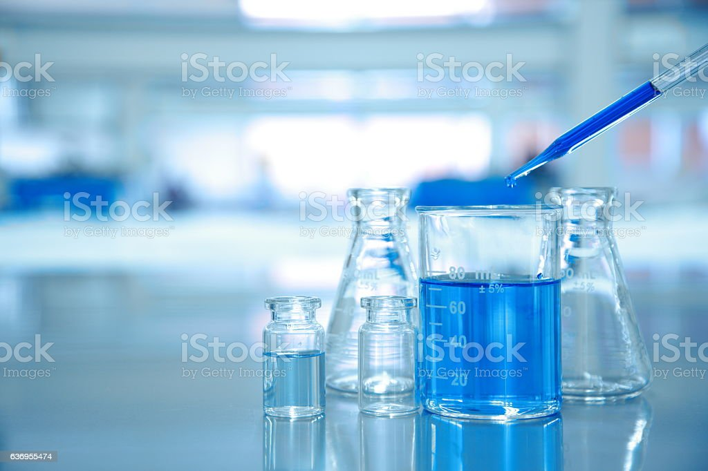 blue drop into glass beaker with flask and science laboratory stock photo