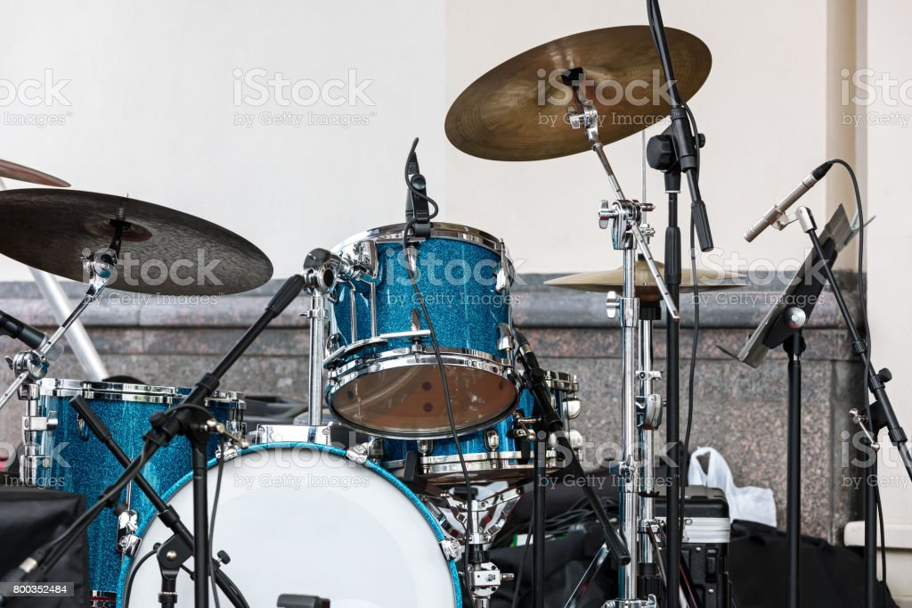 blue drum set and cymbals standing on outdoor stage against wall...
