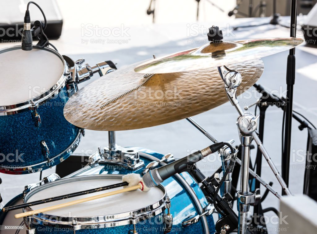 blue drum set with two wooden drumsticks on it. musical instruments on stage ready for the gig. stock photo