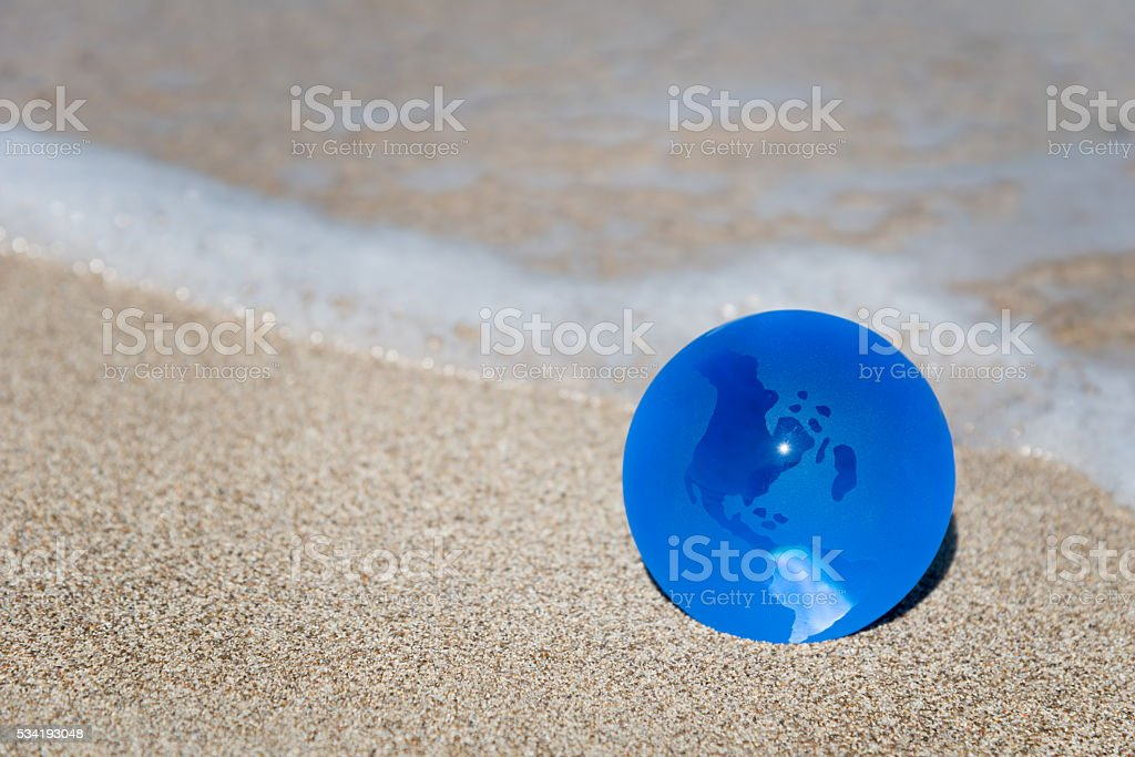 blue earth globe at sandy beach - ecology concept stock photo