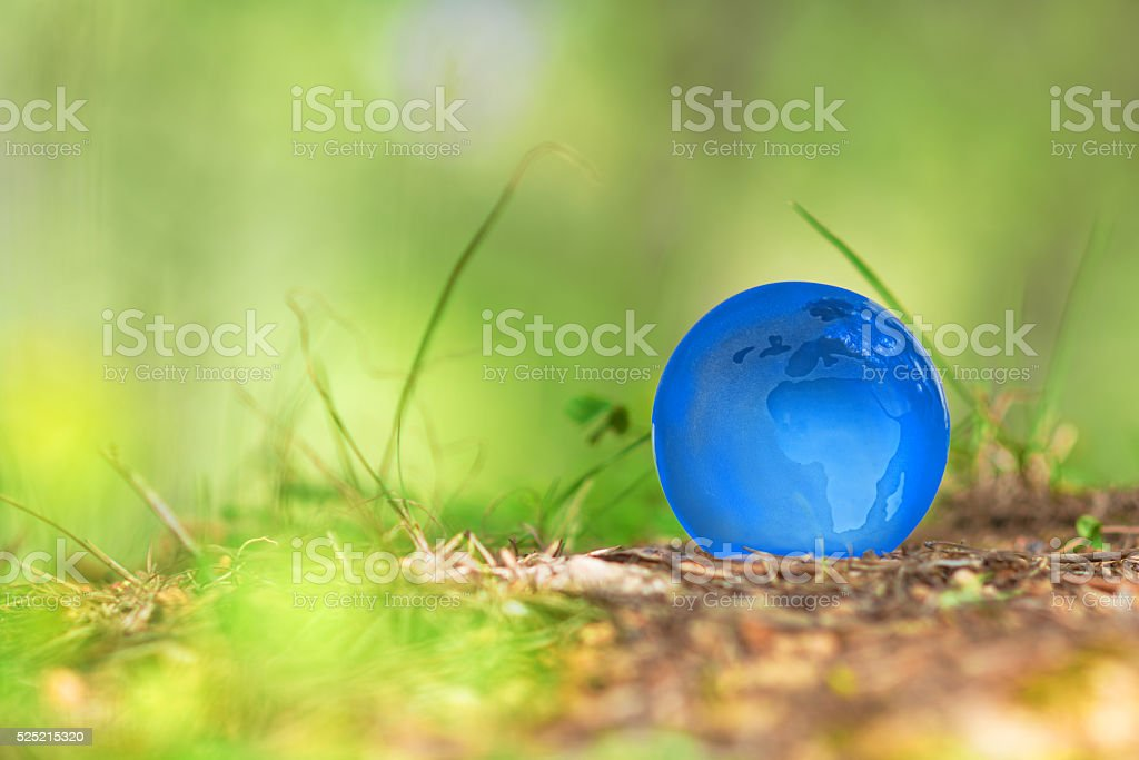 blue earth globe in green nature - ecology concept stock photo
