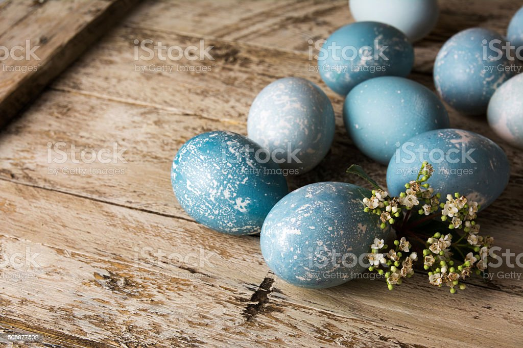 Blue Easter eggs and bouquet of flowers wooden table stock photo