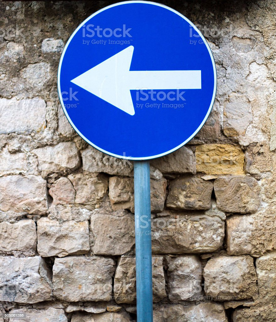 Blue European One-Way Sign Against Old Stone Wall stock photo