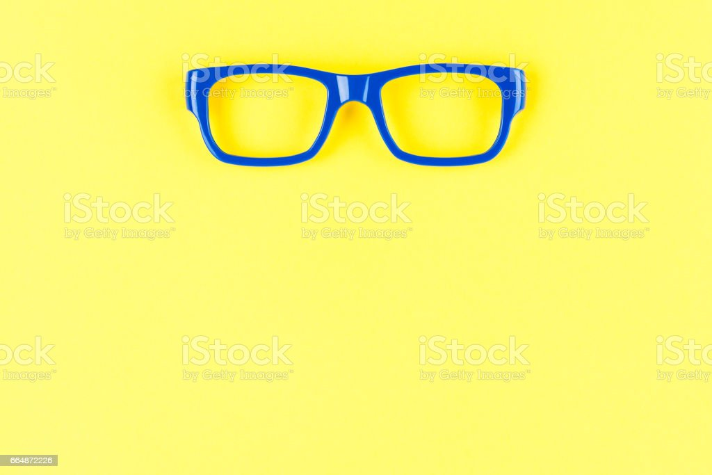 Blue eye glasses on yellow background. Advertising area concept stock photo