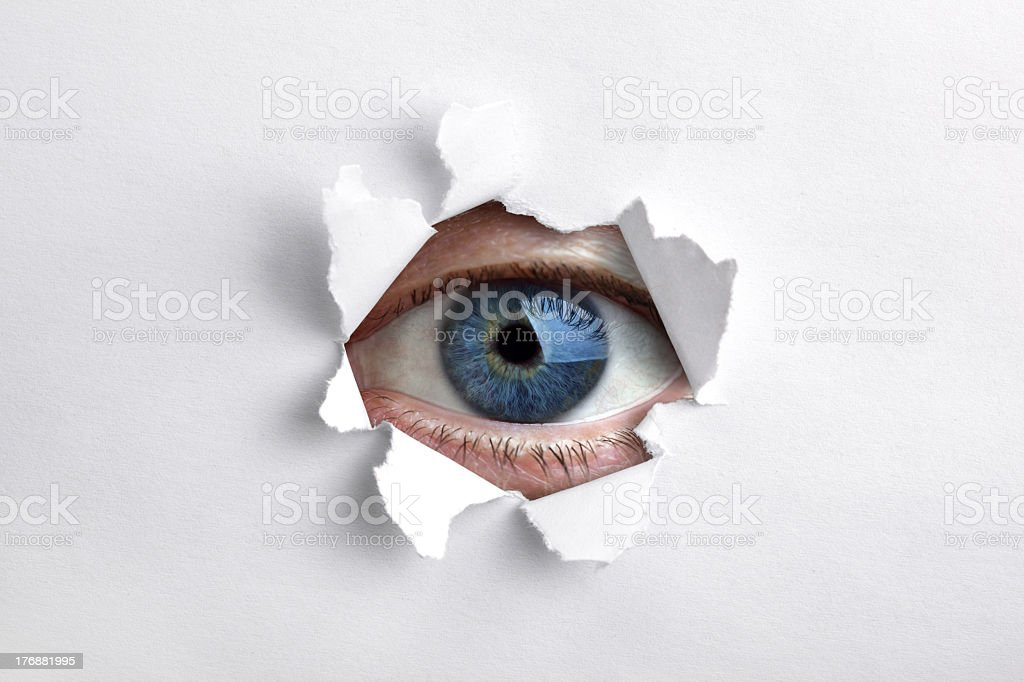 A blue eye looking through a ripped hole in white paper stock photo