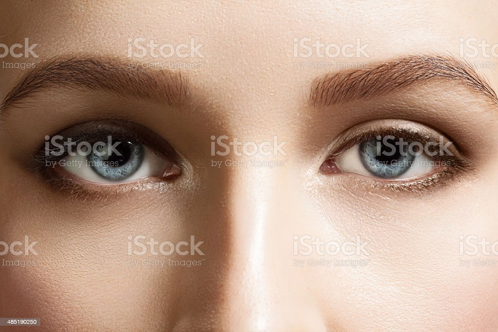 Blue eyes woman with brown eyebrows stock photo