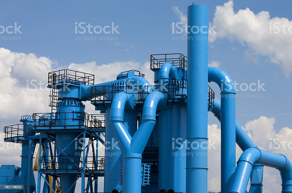 Blue Factory Against Cloudy Sky stock photo