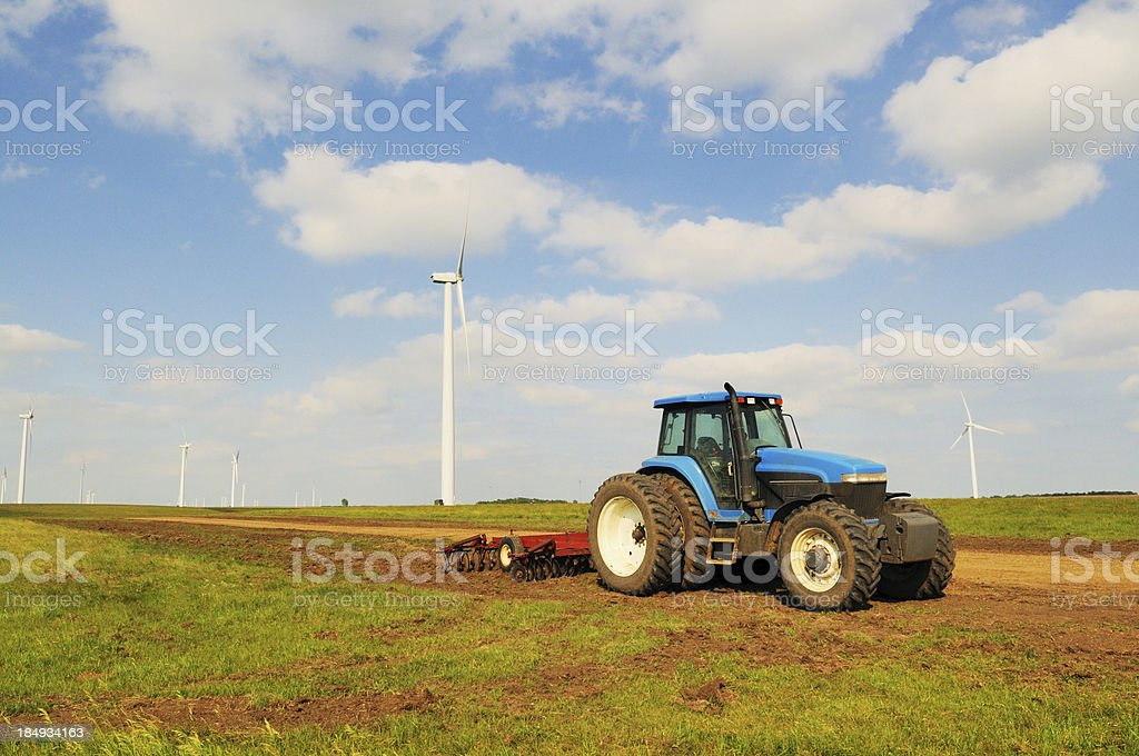 Blue Farm Tractor and Cultivator with Wind Turbine South Dakota royalty-free stock photo