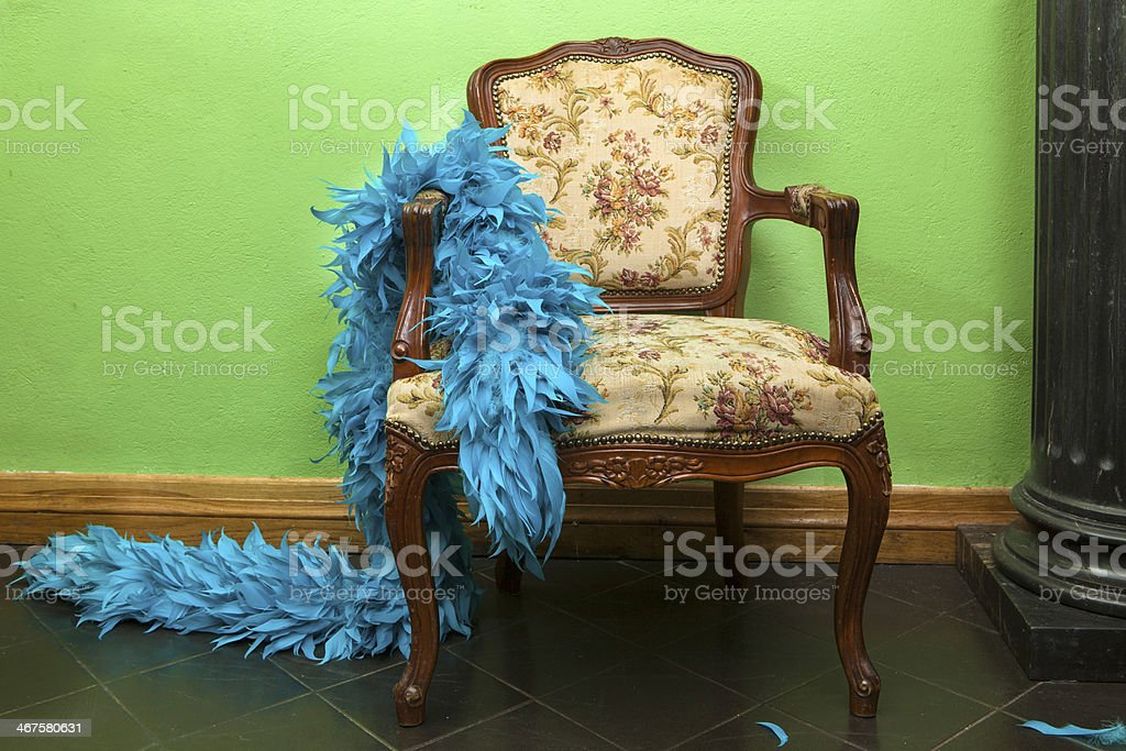 Blue feather boa in the rococo chair stock photo