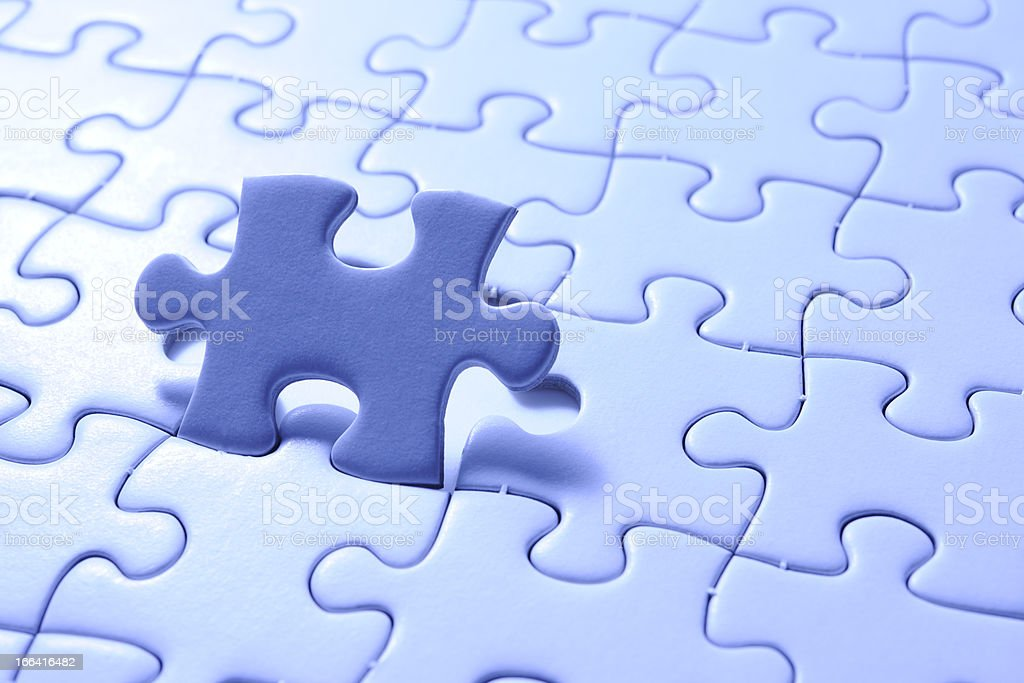 Blue final piece of the jigsaw with light from behind royalty-free stock photo