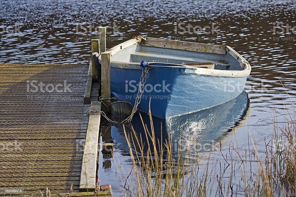 Blue Fishing Boat Moored on Semi-Frozen Lake Landscape royalty-free stock photo
