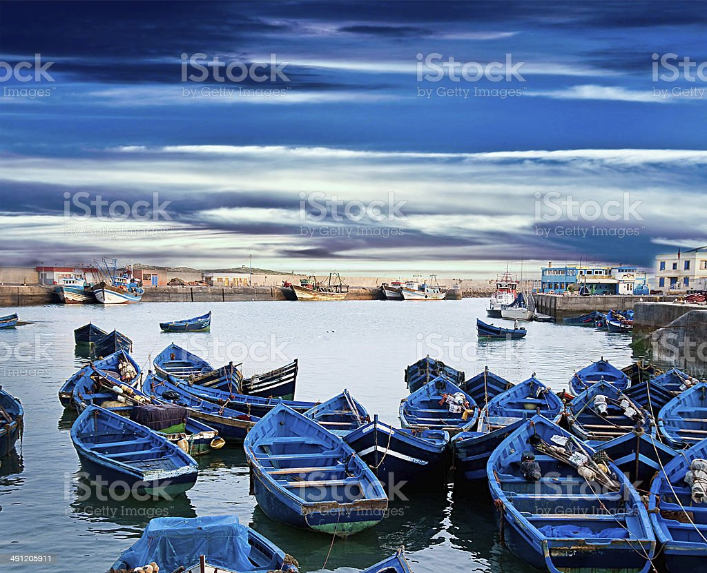 Blue fishing boats on an ocean coast in Essaouira stock photo