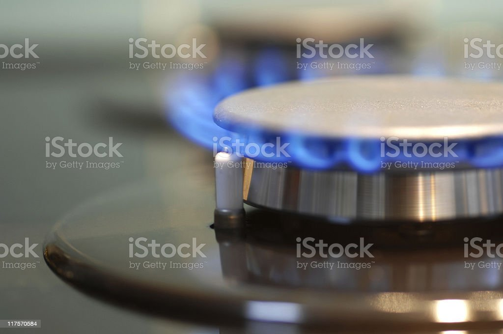 Blue flame coming from a burner on a gas stove stock photo