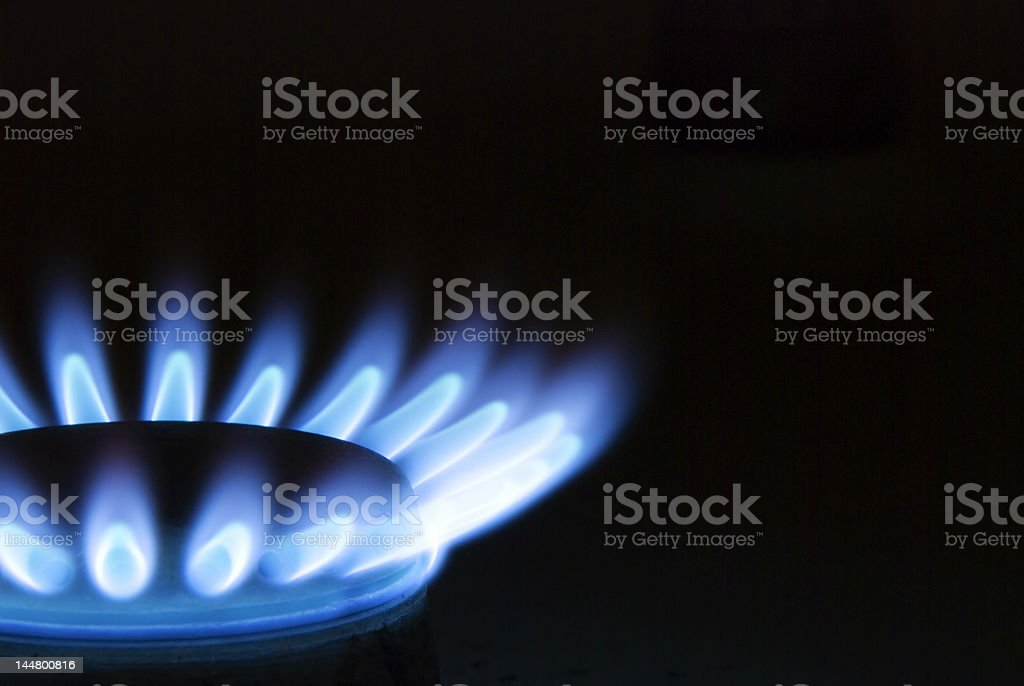 Blue flames coming from gas oven stove with black background royalty-free stock photo