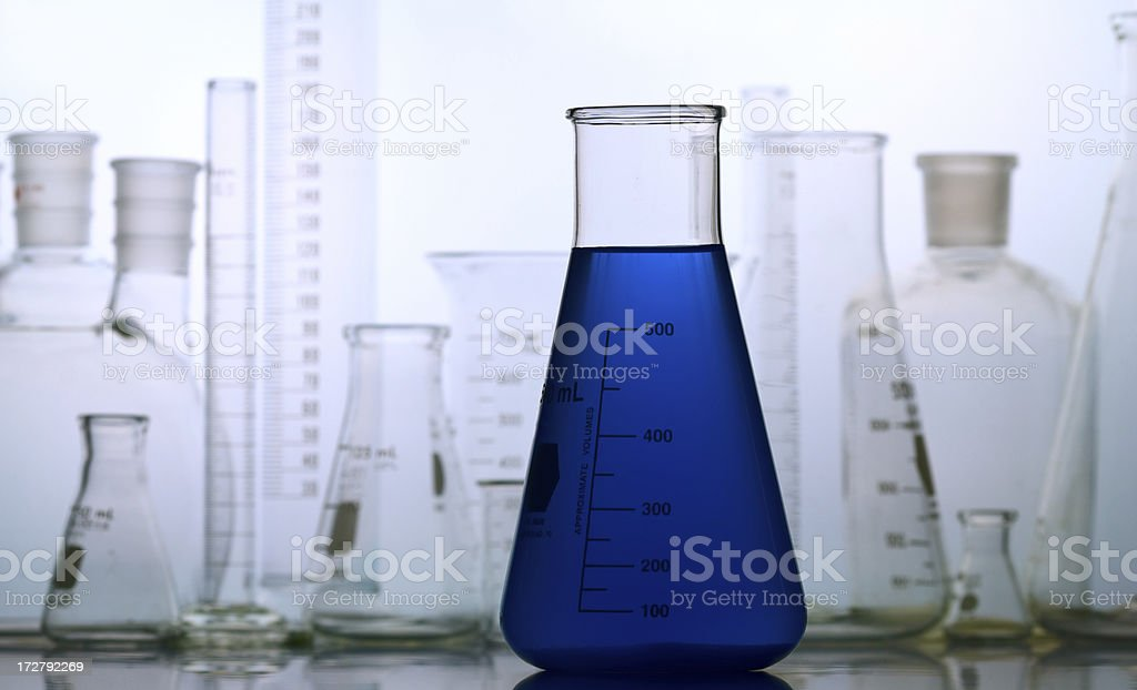 Blue Flask with Lab Glass Background royalty-free stock photo