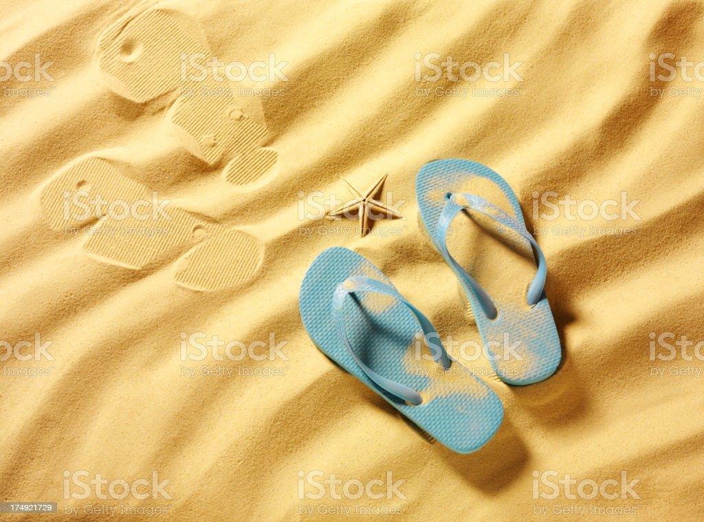 Blue Flip Flops with a Starfish in the Sand royalty-free stock photo
