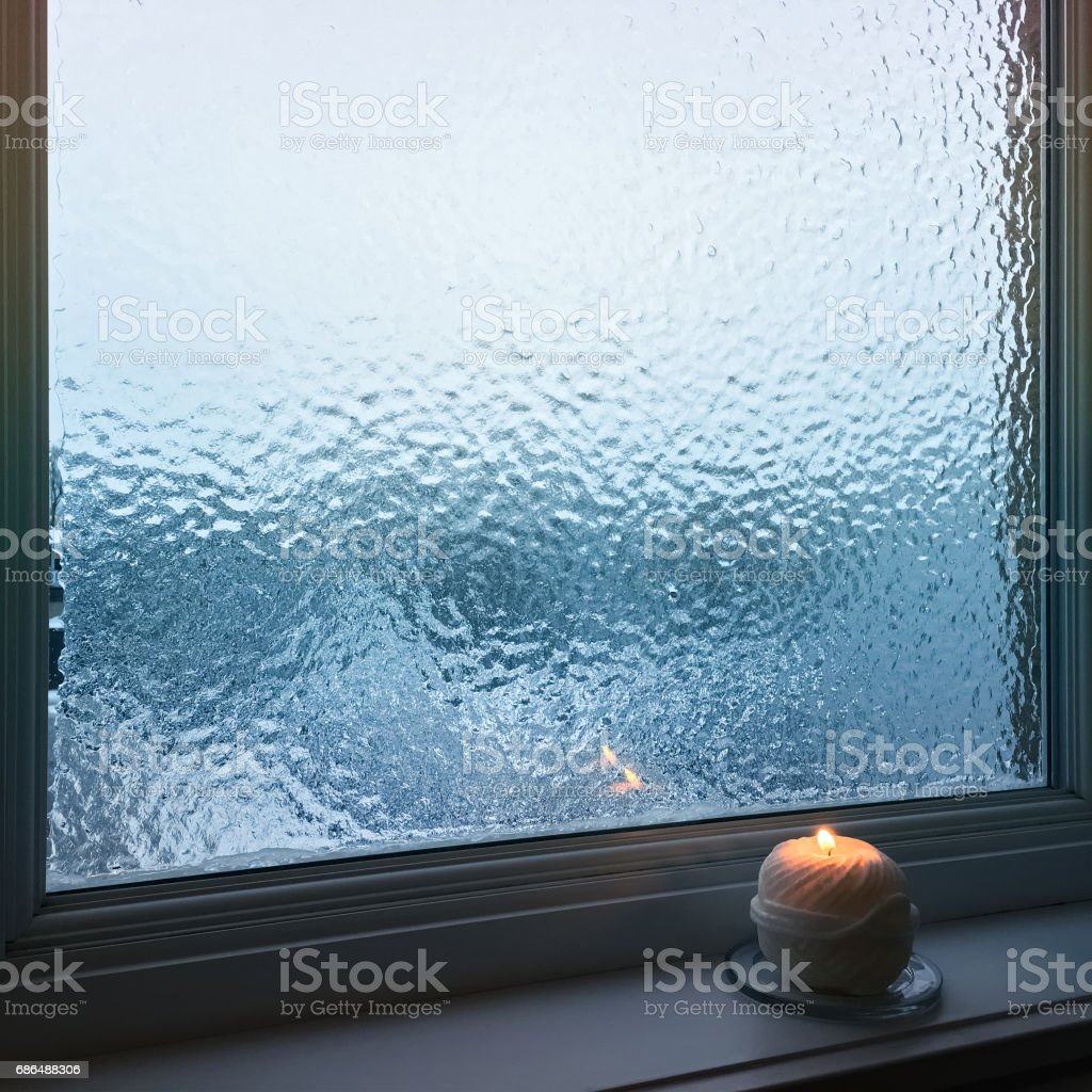 Blue frosted window and cozy candlelight stock photo