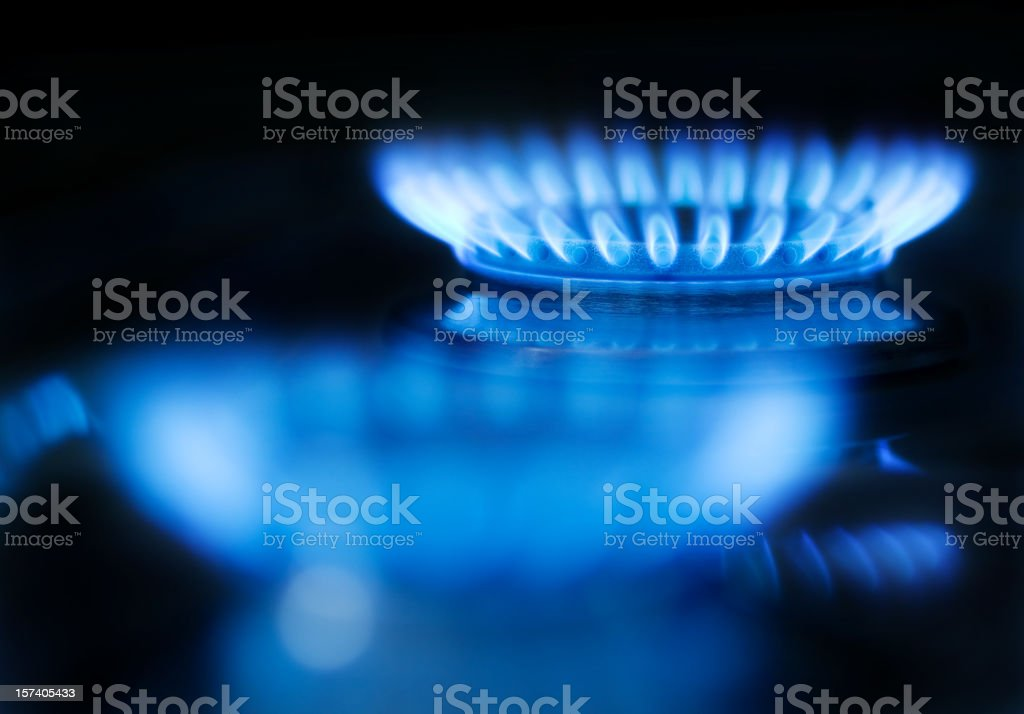 Blue gas flame on a black background stock photo