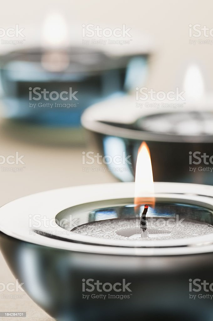 Blue glass candle holders with lit tea light candles royalty-free stock photo