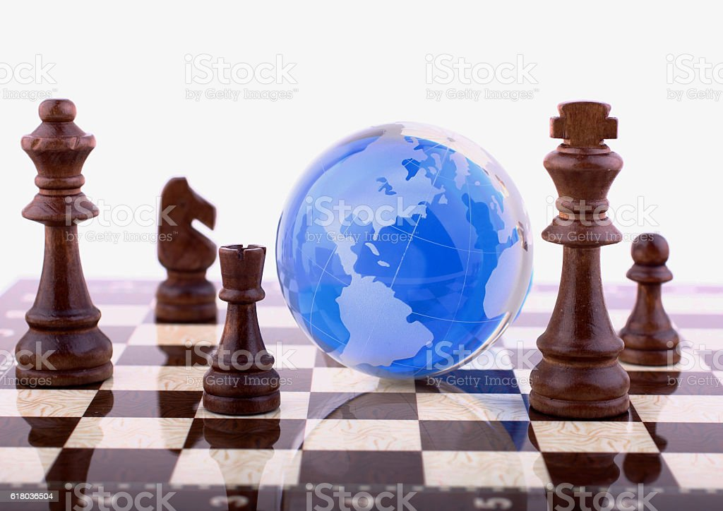 Blue globe on chessboard stock photo