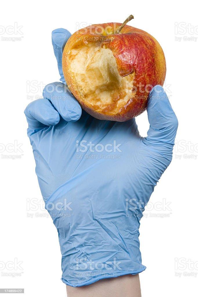 blue glove holding a rotten apple XXXL stock photo