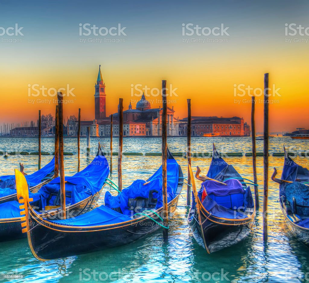blue gondolas under a colorful sunset stock photo