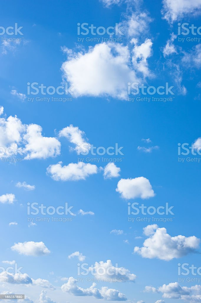 A blue gradient sky with many small puffy cumulus clouds royalty-free stock photo