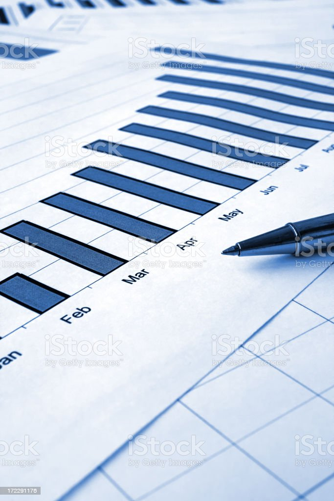 Blue graph for months on white paper next to pen royalty-free stock photo