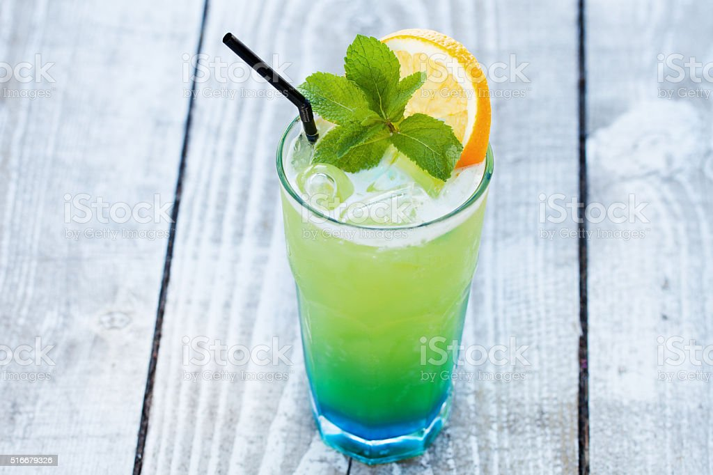blue green cocktail with orange and mint stock photo