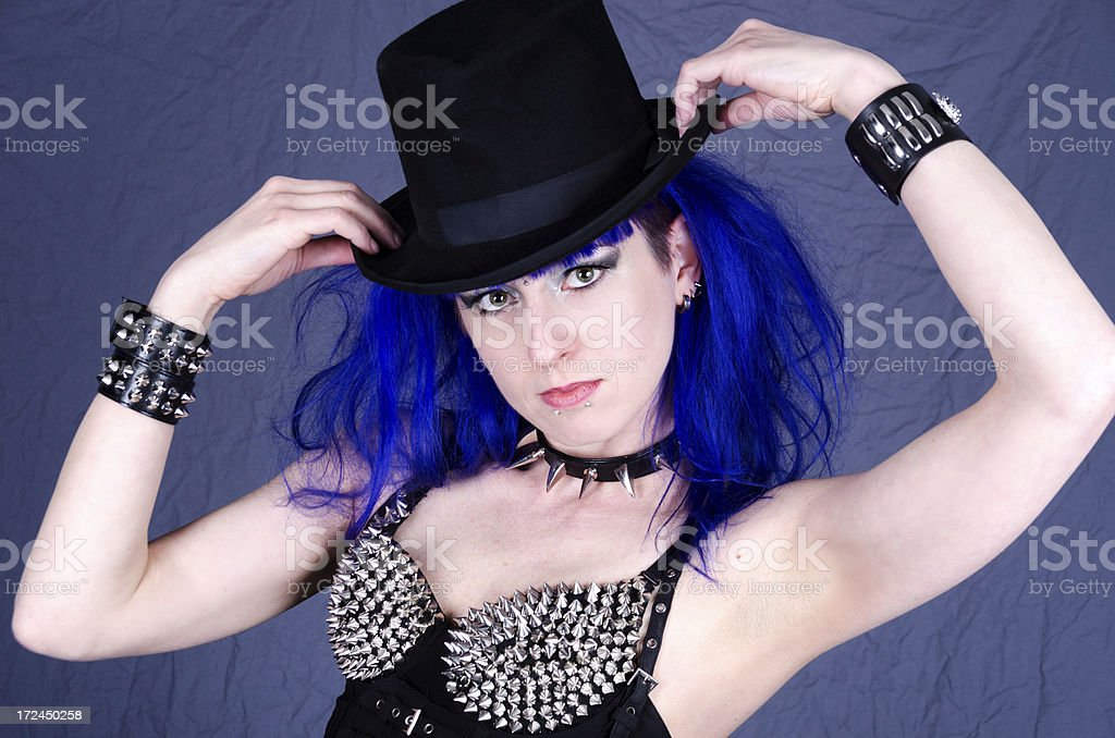Blue haired woman holding brim of top hat. royalty-free stock photo