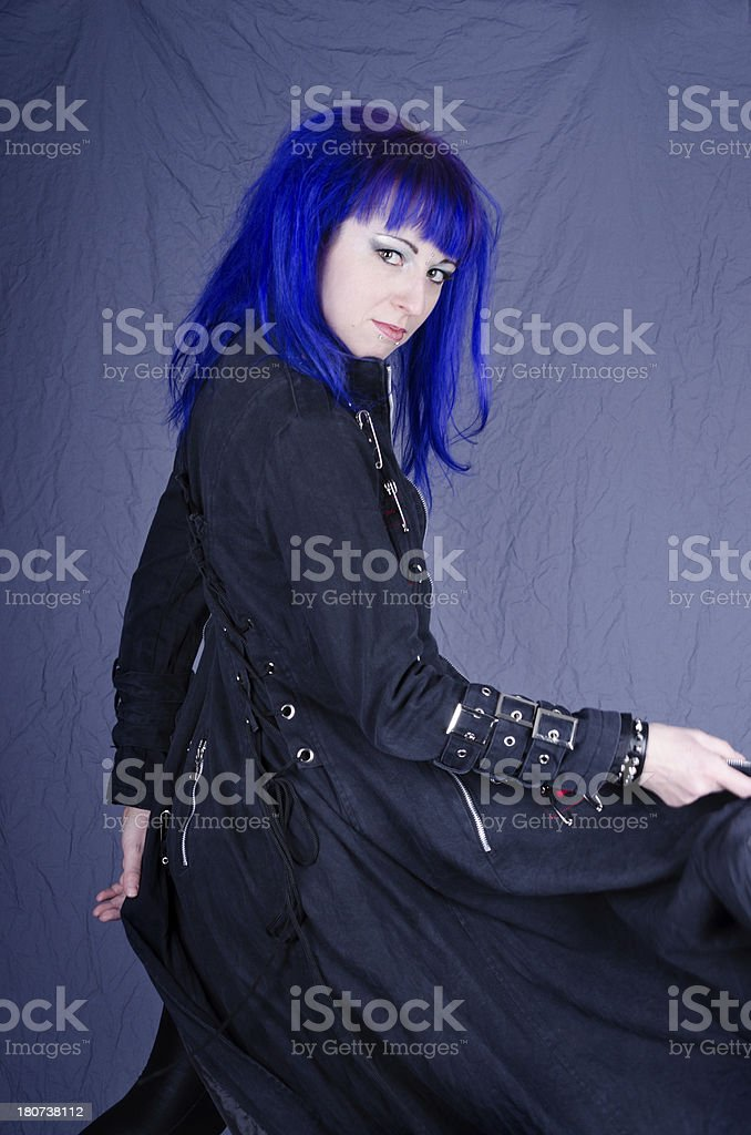 Blue haired woman swirling coat in dramatic exit. royalty-free stock photo