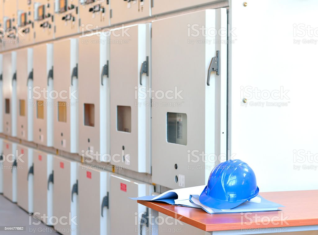 Blue Hardhat on Blueprints in Electrical Room stock photo