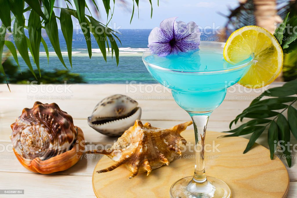 Blue Hawaiian cocktail on the tropical sea background stock photo