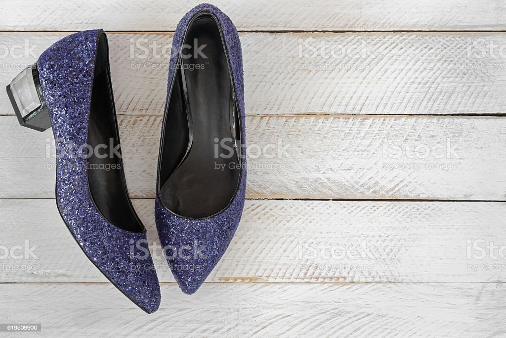 Blue high-heeled shoes with glitters on white wooden background stock photo