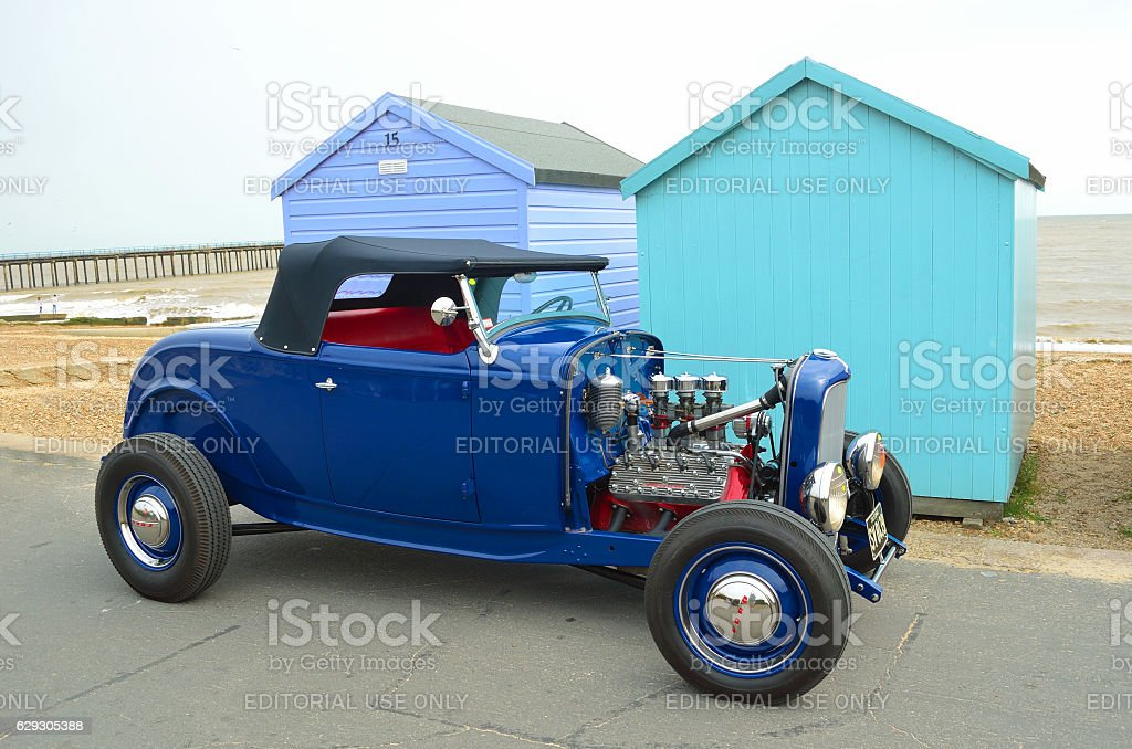 Blue Hot rod parked in front of beach huts stock photo