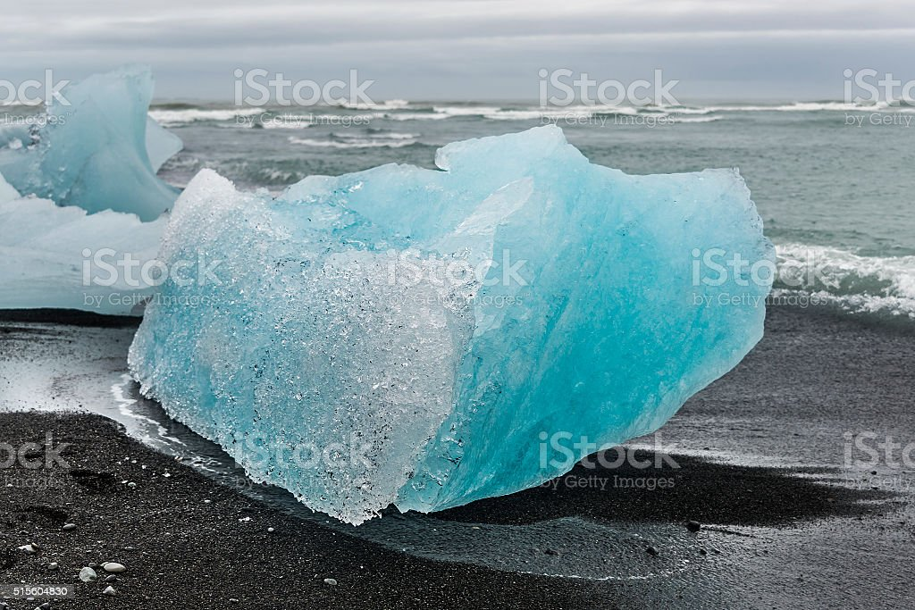 Blue ice at glacier lagoon and black beach on Iceland stock photo