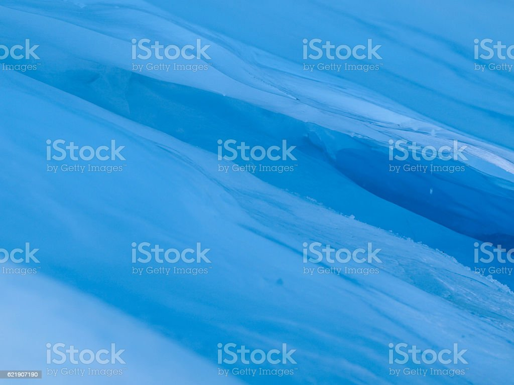 blue ice cave covered with snow and flooded with light stock photo