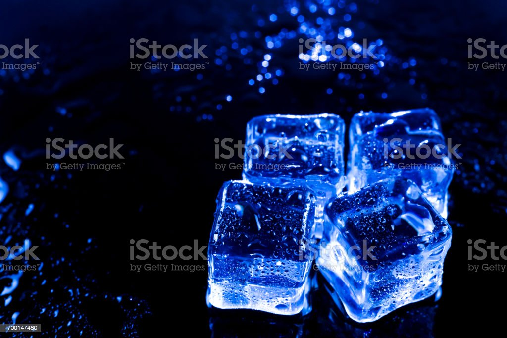 Blue ice cubes on black wet table. stock photo