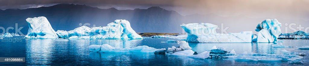 Blue icebergs floating along storm Arctic coast panorama Jokulsarlon Iceland stock photo