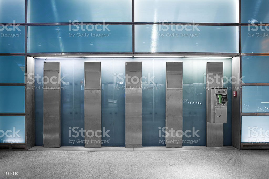 Blue illuminated glass wall - subway station, public phone stock photo