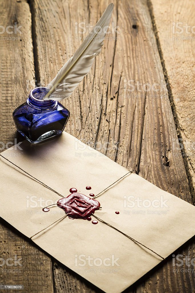 Blue ink inkwell with feather on envelope and red sealant royalty-free stock photo