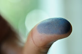 blue ink on thumb finger