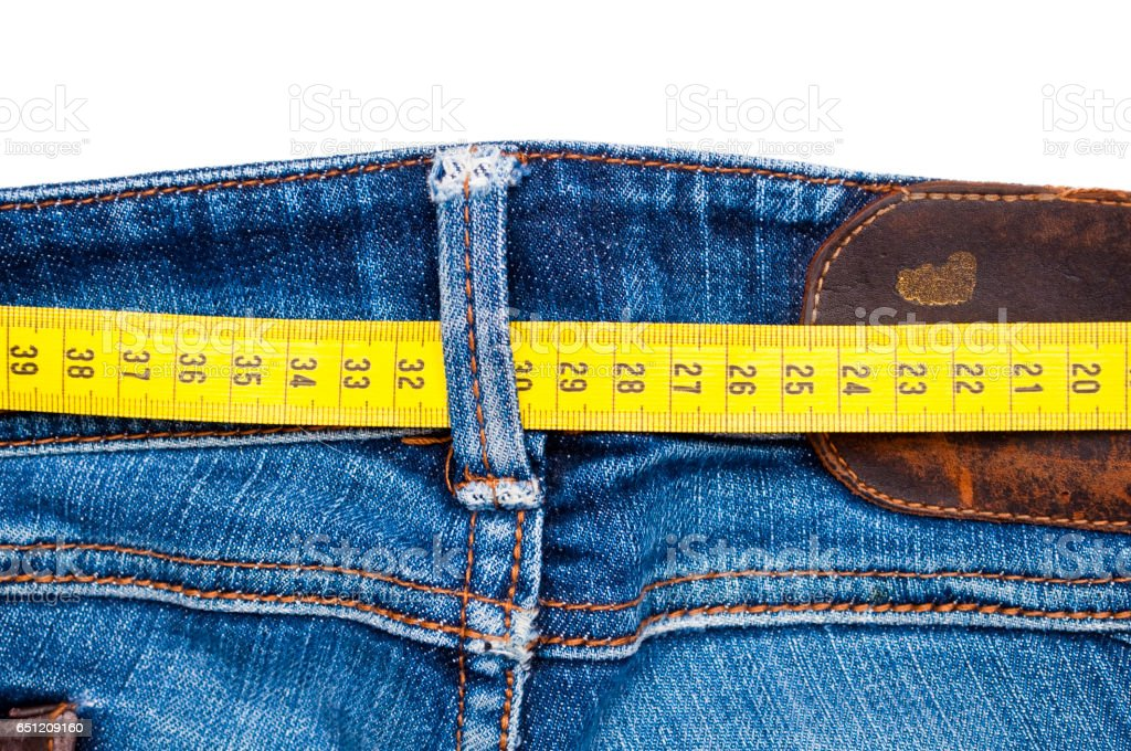 Blue jeans and measure tape isolated - concept of overweight stock photo