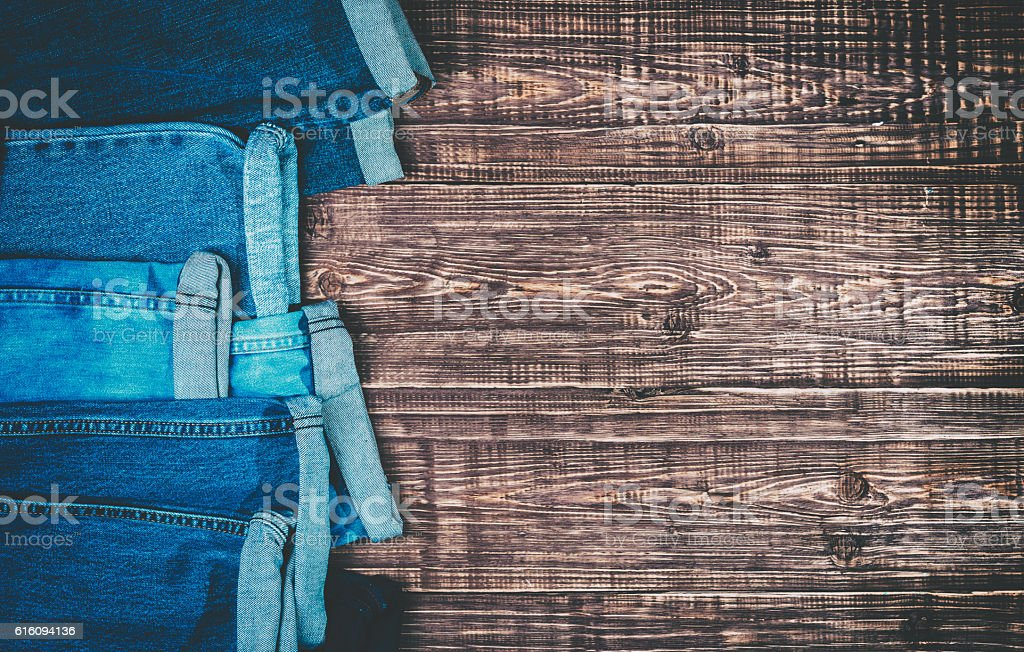 Blue jeans on a brown wooden background. stock photo